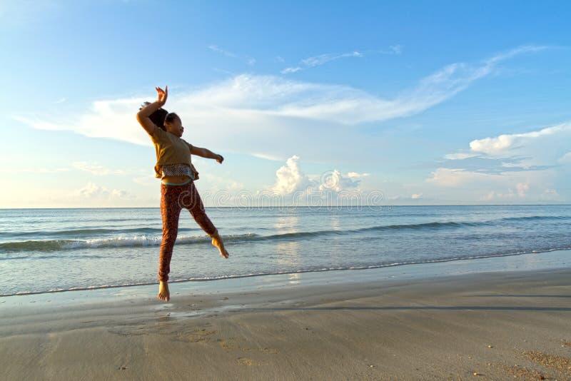 Gladlynt flicka på stranden på gryning royaltyfri fotografi