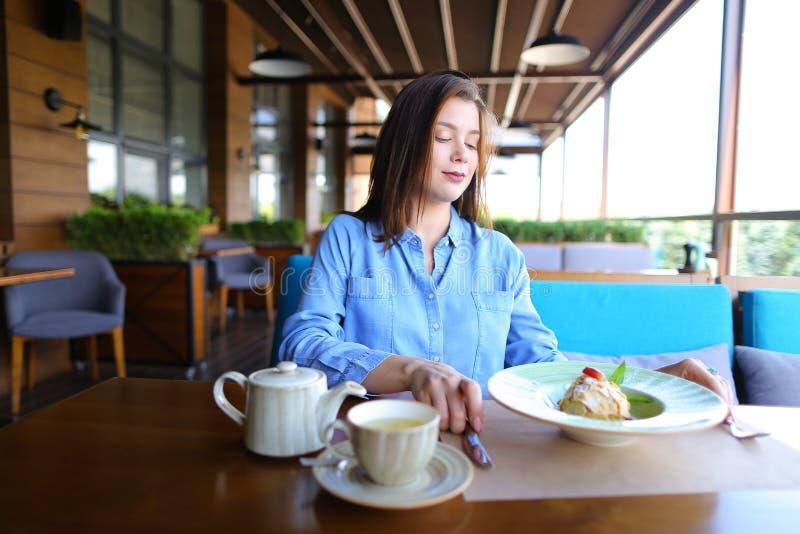 Gladlynt flicka som bläddrar vid smartphonen på kafét och äter desser royaltyfria bilder