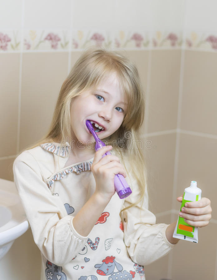 Gladlynt flicka som borstar hennes tänder i den nya tandborsten för badrum arkivfoton