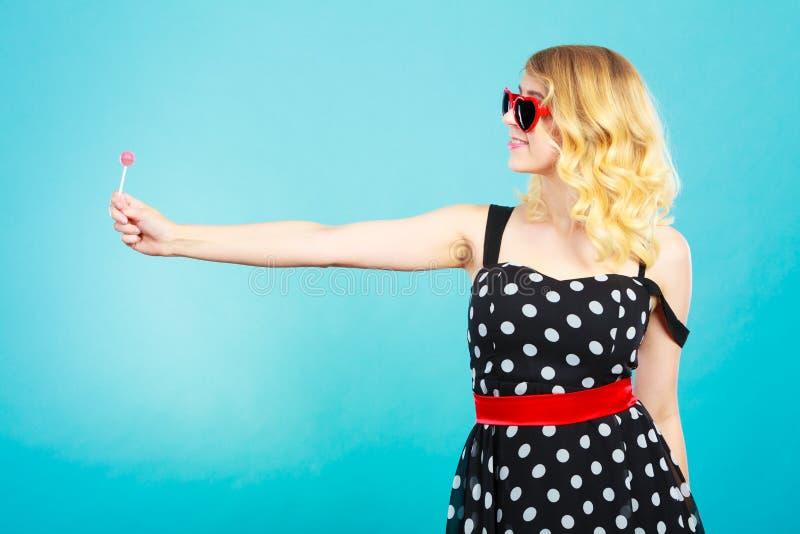 Gladlynt flicka som rymmer den lilla klubbagodisen i hand arkivbilder