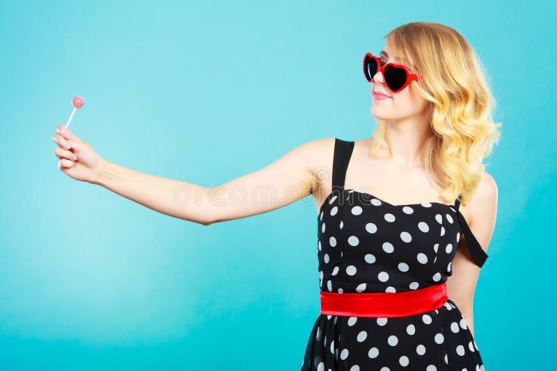 Gladlynt flicka som rymmer den lilla klubbagodisen i hand arkivbild