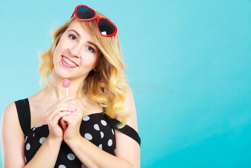 Gladlynt flicka som rymmer den lilla klubbagodisen i hand arkivfoto