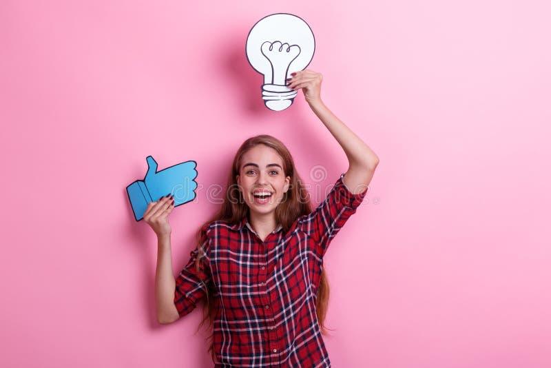 Gladlynt flicka som rymmer en bild av en ljus kula och ett tecken av den övre tummen och att skratta royaltyfria foton