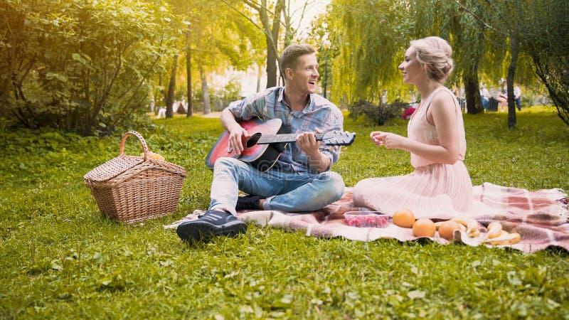 Gladlynt flicka som sjunger joyfully sånger med hennes pojkvän som spelar gitarren, datum arkivfoto