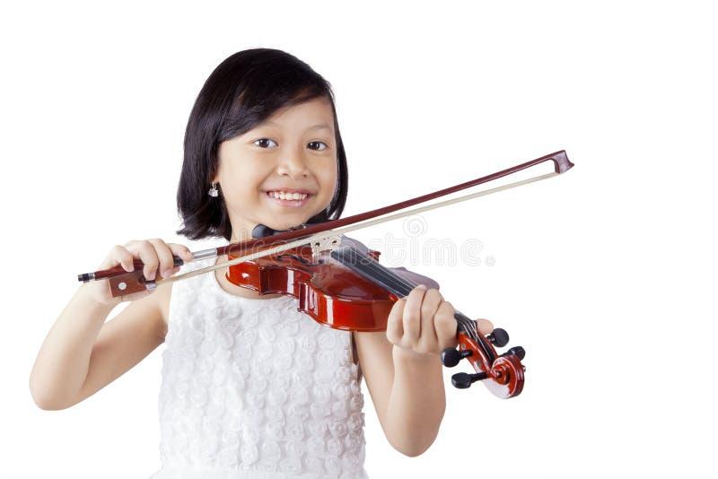 Gladlynt flicka som spelar fiolen i studion royaltyfria foton