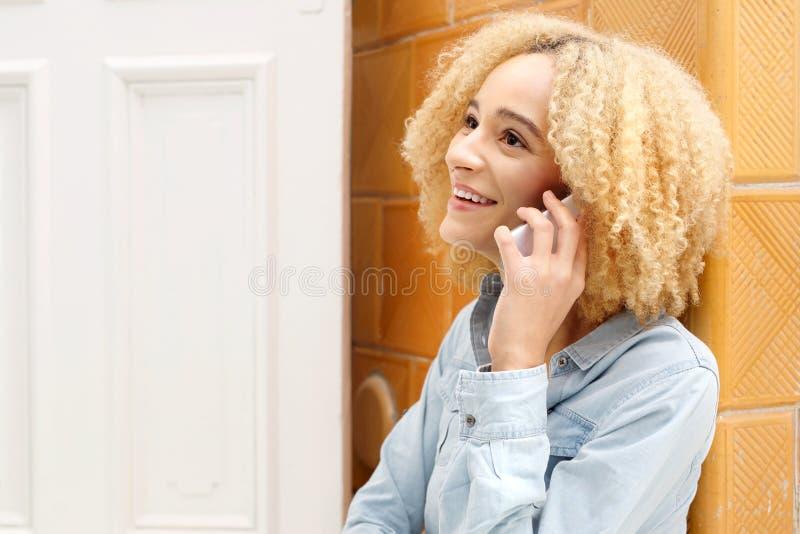 Gladlynt flicka som talar på en mobiltelefon fotografering för bildbyråer