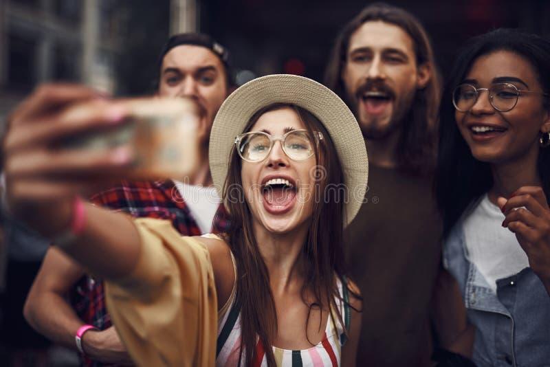 Gladlynt flicka som tar selfie medan vänner som bakom står fotografering för bildbyråer