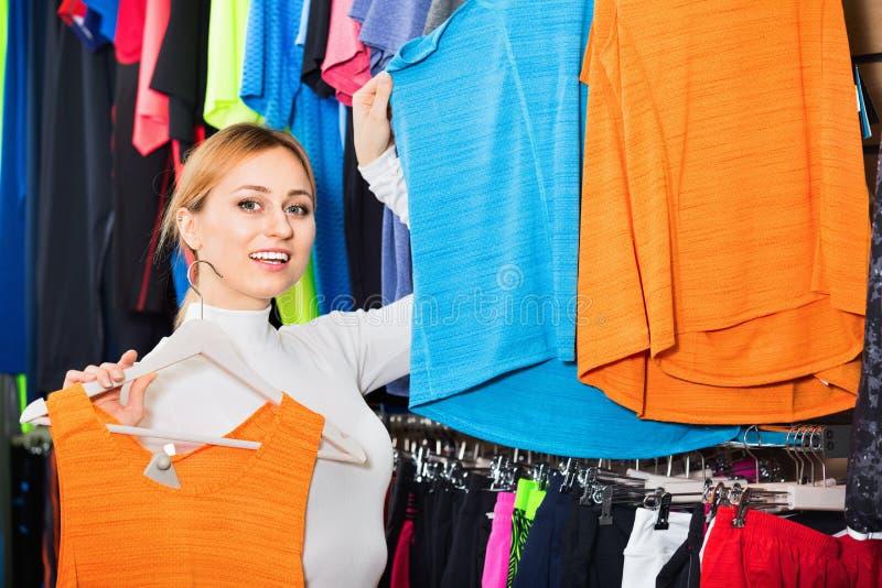 Gladlynt flicka som väljer enskjorta i lagret royaltyfria bilder