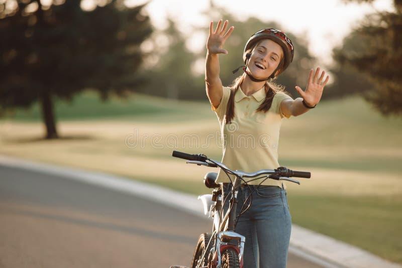 Gladlynt flickacyklist som utomhus gör en gest med händer royaltyfria bilder