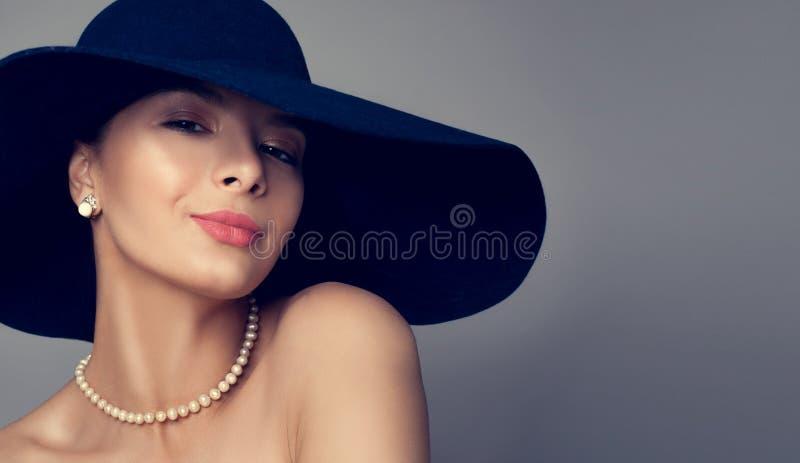 Gladlynt flickamodemodell i hattstående royaltyfri fotografi