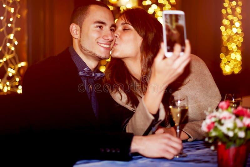 Gladlynt flickvän som kysser hennes pojkvän på kinden, medan ta självståenden royaltyfri foto