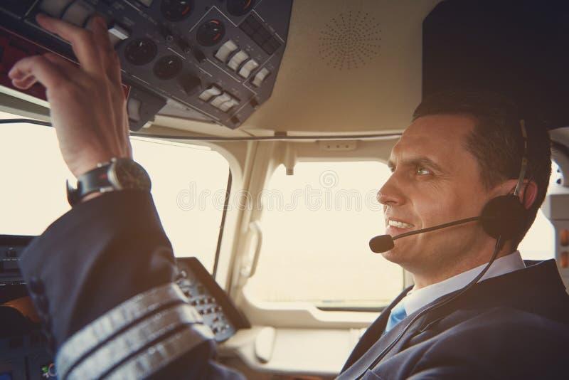 Gladlynt flygare som trycker på knappar i cockpit royaltyfri foto