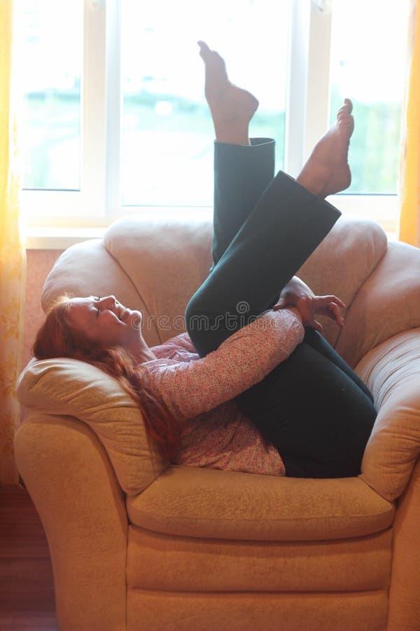 Gladlynt fyllig flicka som omkring bedrar på soffan arkivfoton