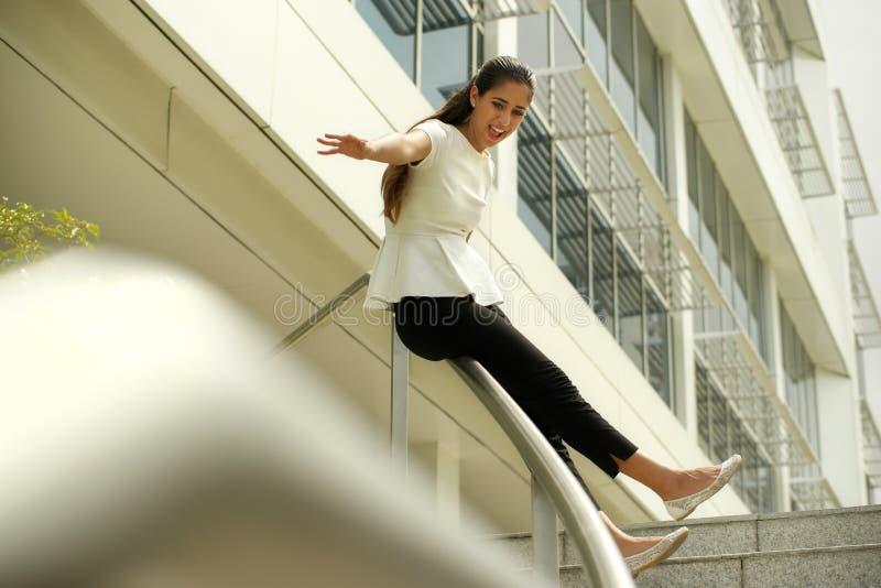Gladlynt gående bottenvåning för affärskvinna som glider på stången för glädje royaltyfri bild