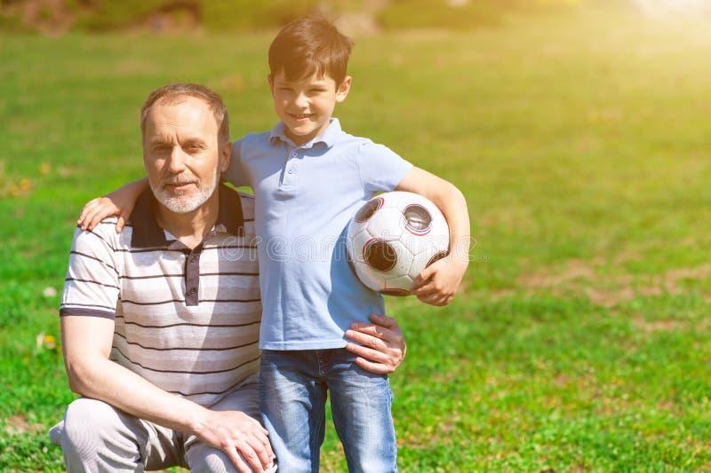Gladlynt gamal man och hans barnbarn som spelar fotboll arkivbilder