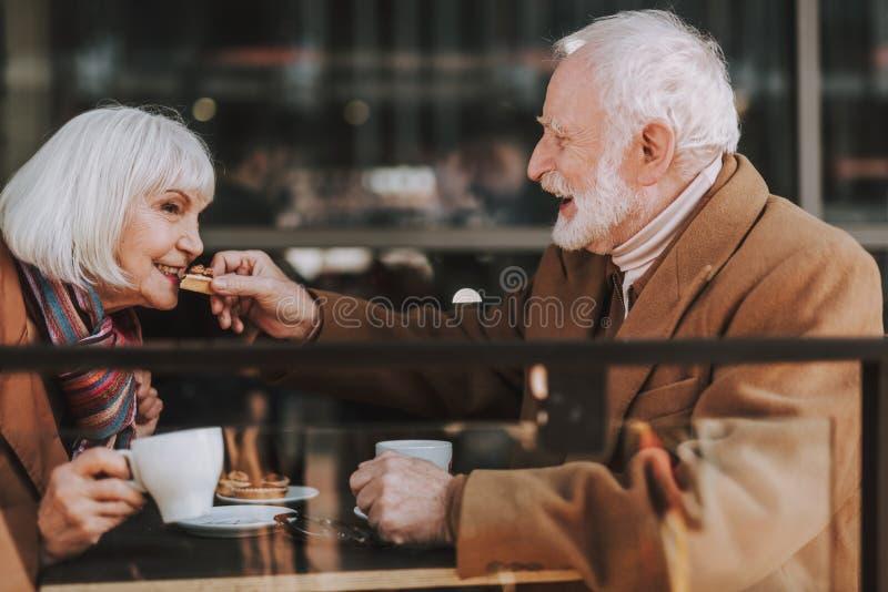Gladlynt gammal gentleman som matar hans fru med den läckra kakan royaltyfri foto