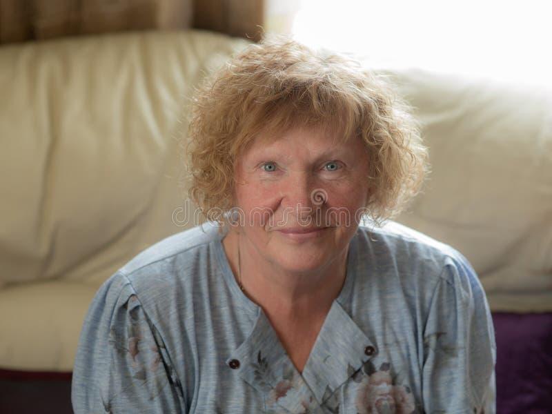 Gladlynt gammal kvinna hemma royaltyfri foto