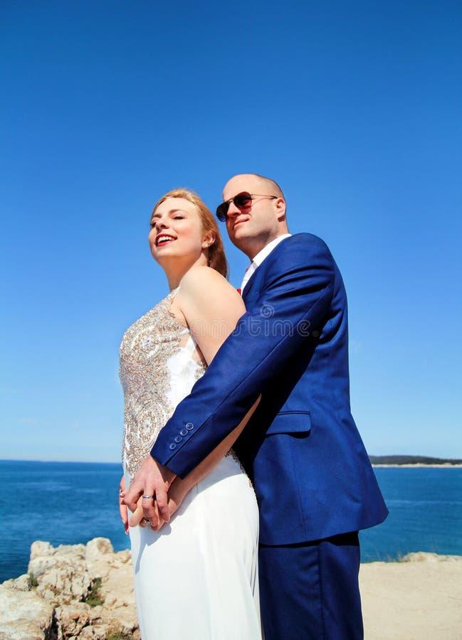 Gladlynt gift paranseende på stranden royaltyfri fotografi