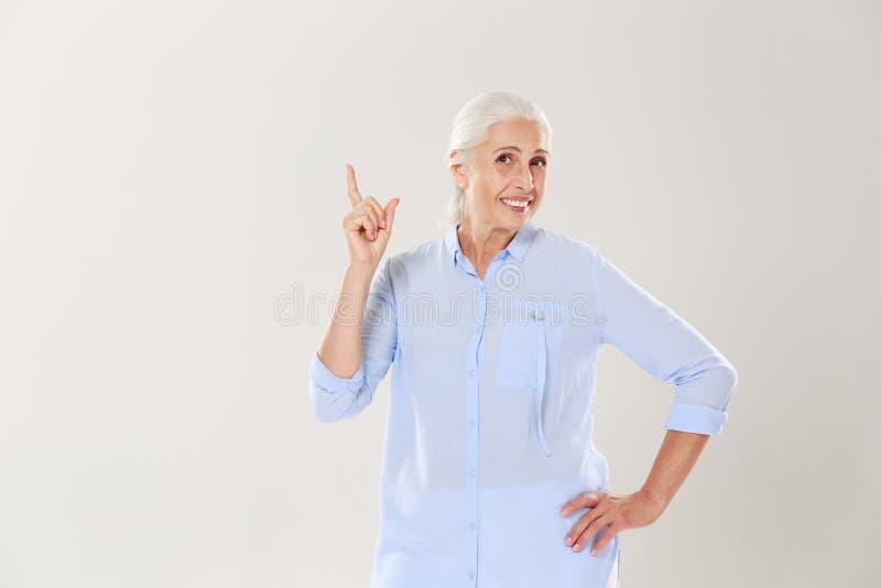 Gladlynt gråhårig gammal dam i den blåa skjortan som pekar med finge royaltyfri bild