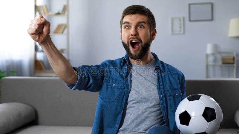 Gladlynt grabb som skriker högt den hållande ögonen på fotbollsmatchen, lyckat modigt resultat arkivfoton