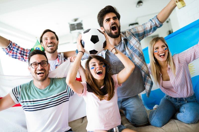 Gladlynt grupp av vänner som håller ögonen på fotbollleken på tv arkivfoto