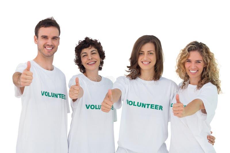 Gladlynt grupp av volontärer som ger upp thums arkivbild