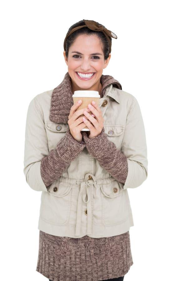Gladlynt gullig brunett i vintermode som rymmer den disponibla koppen royaltyfri bild
