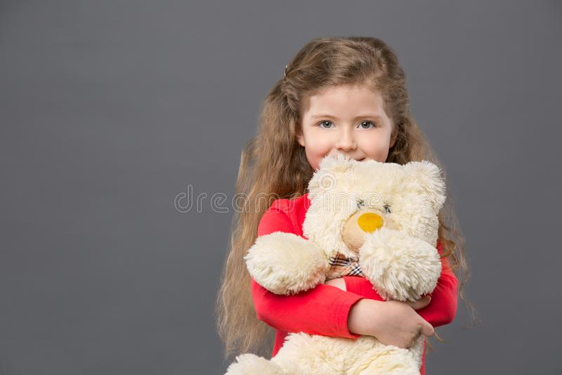 Gladlynt gullig flicka som rymmer hennes favorit- leksak royaltyfria bilder