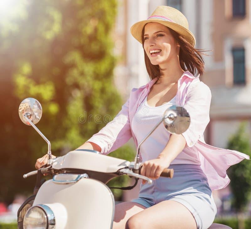 Gladlynt gullig kvinnaridningsparkcykel i sommarstad royaltyfri bild