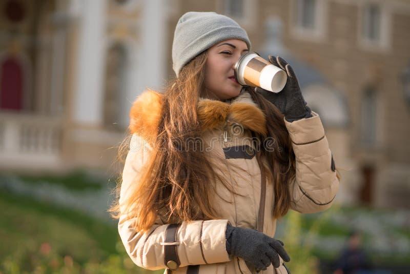 Gladlynt gullig ung kvinna som går på gatan och dricker kaffe arkivfoton