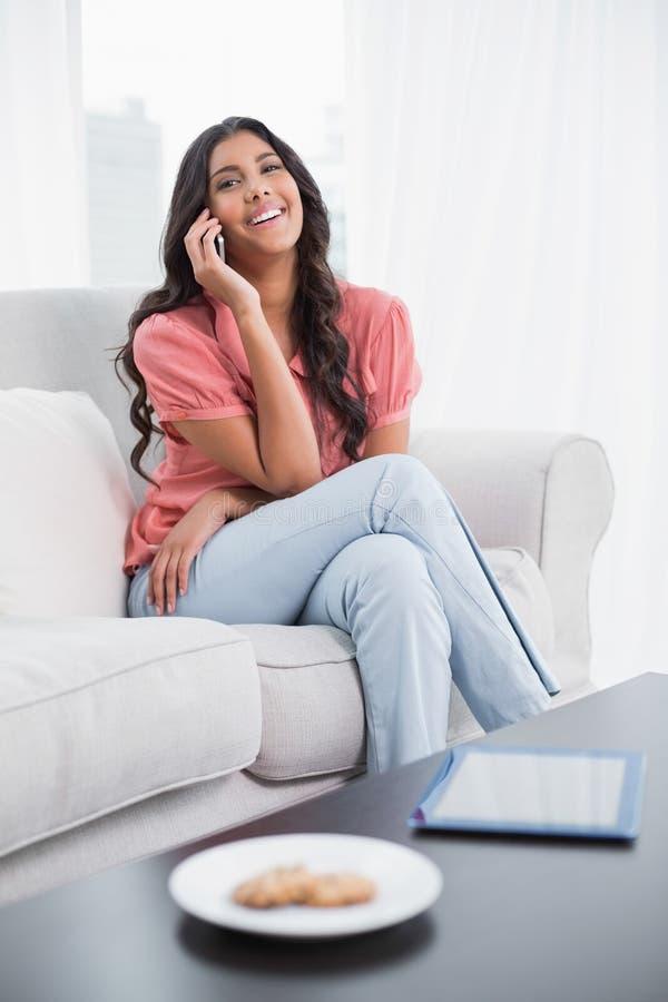 Gladlynt gulligt brunettsammanträde på soffan som ringer på smartphonen royaltyfri bild