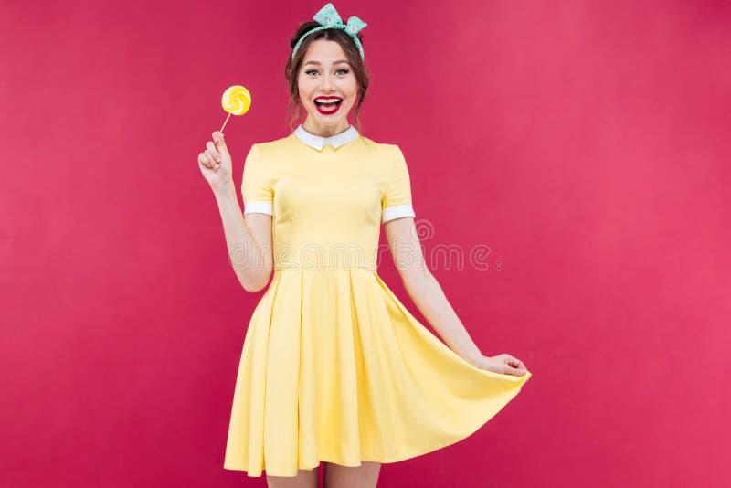 Gladlynt gulligt utvikningsbrudflickaanseende och gul klubba för innehav royaltyfri fotografi