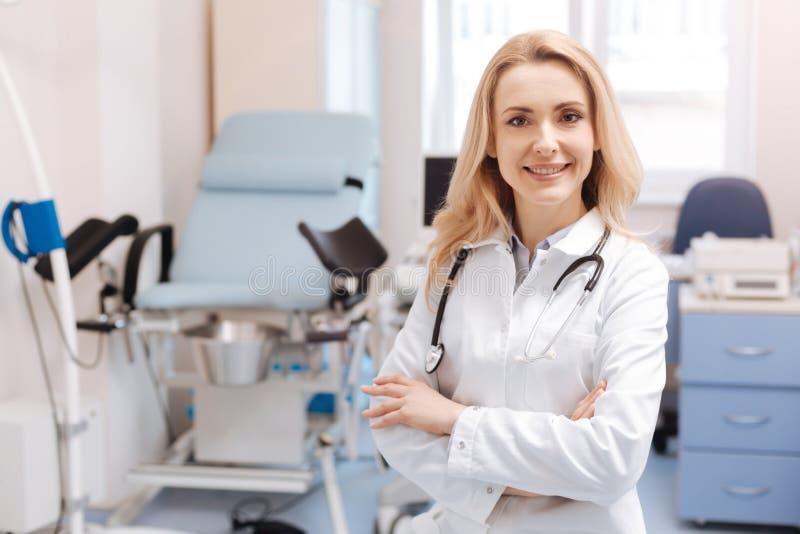 Gladlynt gynekolog som väntar på den nästa patienten i kabinettet royaltyfria bilder
