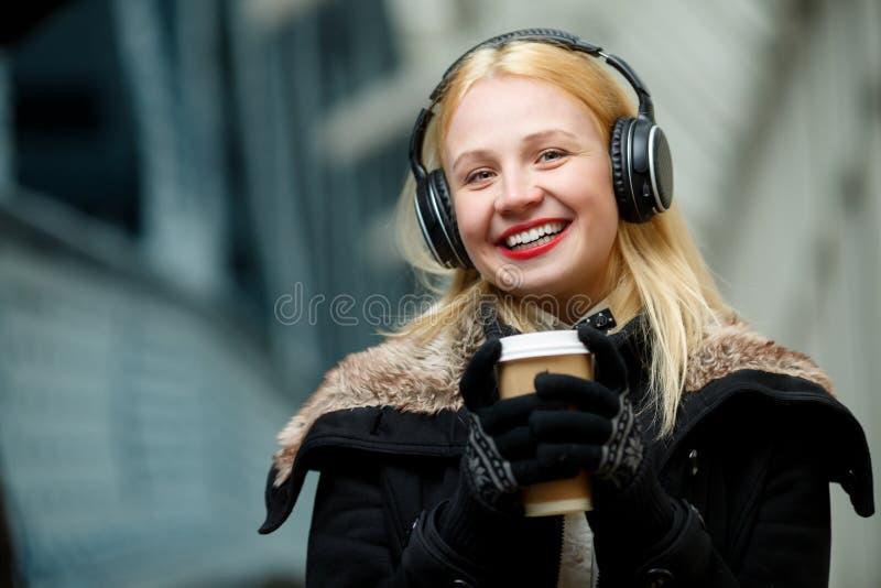 Gladlynt härlig blond kvinna med hörlurar och koppen kaffe royaltyfri bild