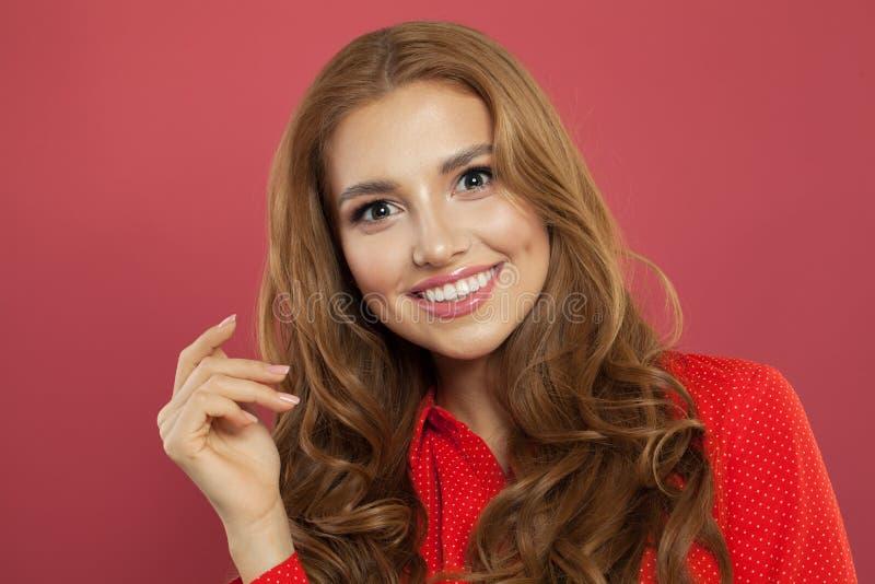 Gladlynt härlig flicka på den rosa ståenden Nätt rött haired le för kvinna royaltyfria bilder