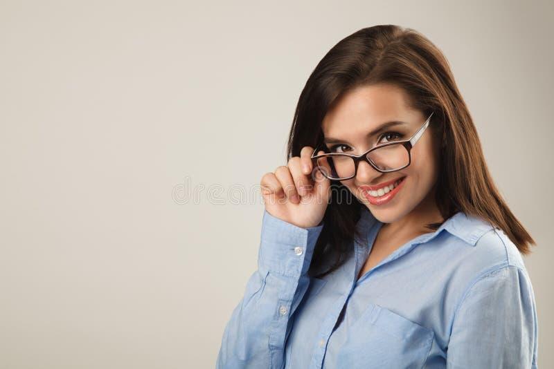 Gladlynt härlig ung affärskvinna i blå skjorta med exponeringsglas arkivfoton