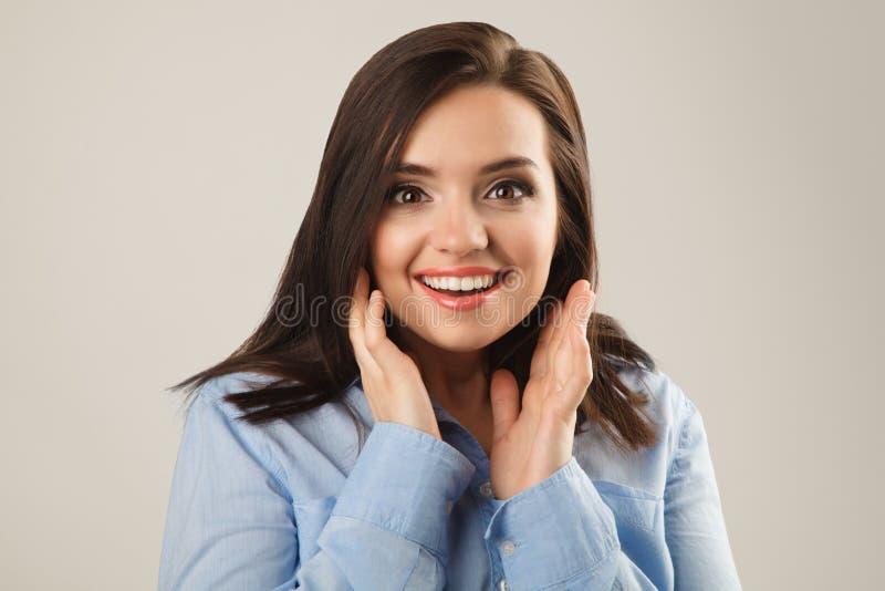 Gladlynt härlig ung affärskvinna i den förvånade blåa skjortan arkivfoto