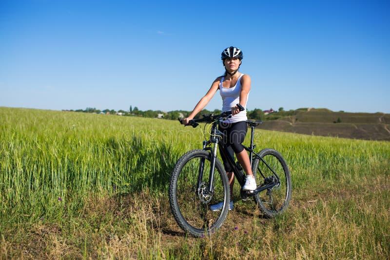 Gladlynt härlig ung kvinna med cykeln och hjälm på fält royaltyfri foto