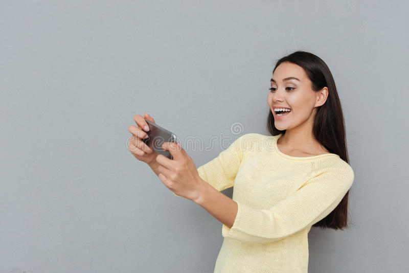 Gladlynt härlig ung kvinna som spelar videospel på mobiltelefonen arkivfoton