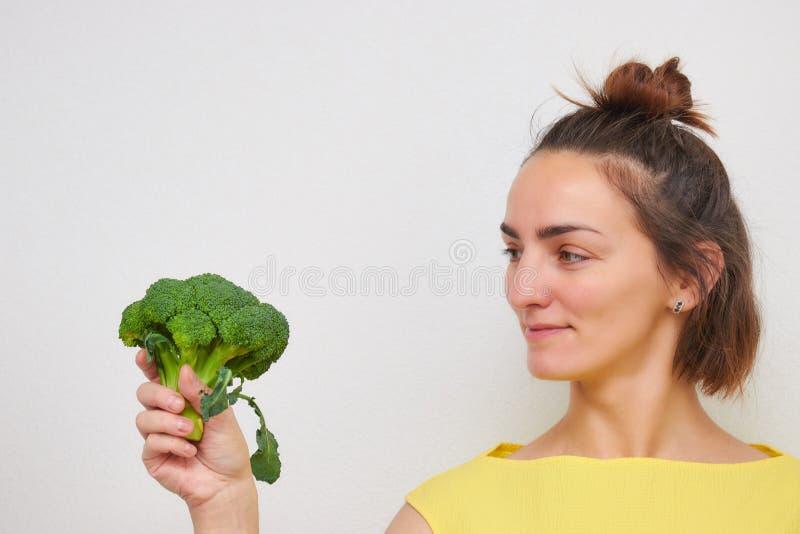 Gladlynt härligt, slankt, flicka som rymmer broccoliinflorescences i hennes händer som isoleras på en ljus bakgrund kvinna av eur arkivfoto