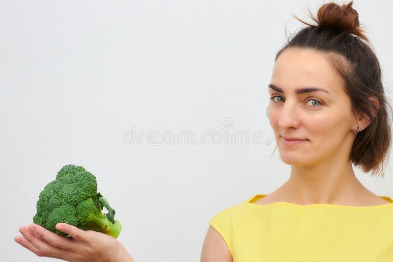 Gladlynt härligt, slankt, flicka som rymmer broccoliinflorescences i hennes händer som isoleras på en ljus bakgrund kvinna av eur arkivbilder