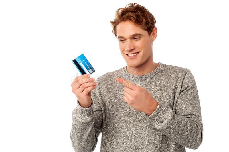 Gladlynt hållande kreditkort för ung man royaltyfria foton