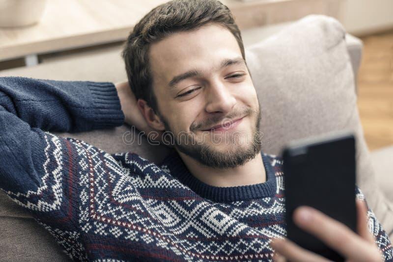 Gladlynt hållande mobiltelefon för ung man och le hemma royaltyfria foton