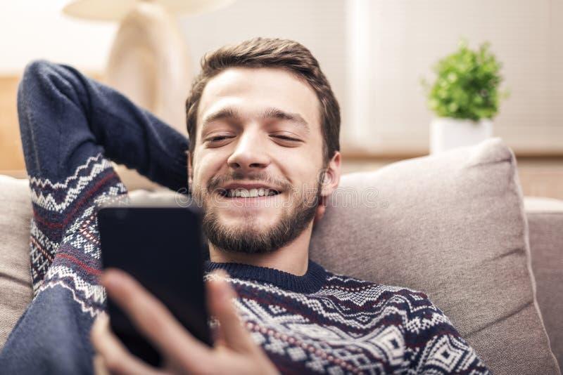 Gladlynt hållande mobiltelefon för ung man och le hemma arkivfoton