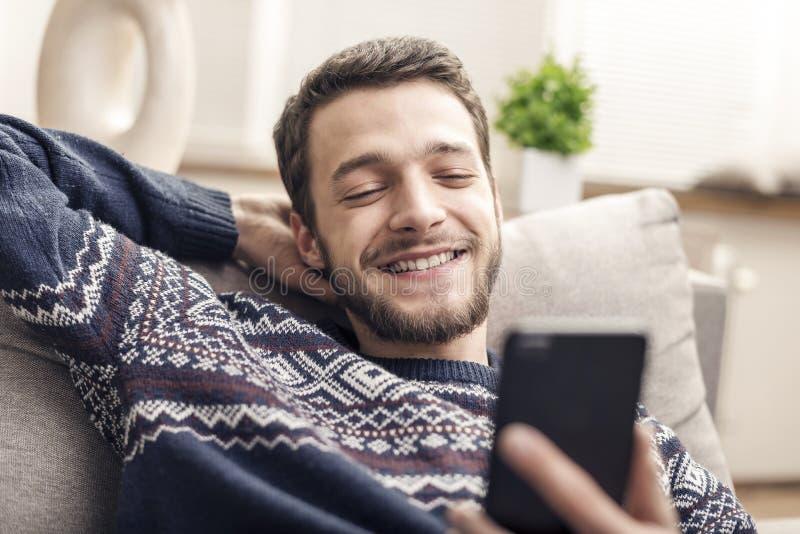 Gladlynt hållande mobiltelefon för ung man och le hemma arkivbild