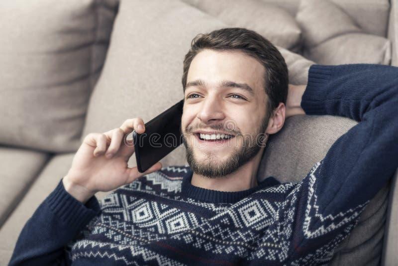 Gladlynt hållande mobiltelefon för ung man och le hemma royaltyfri foto