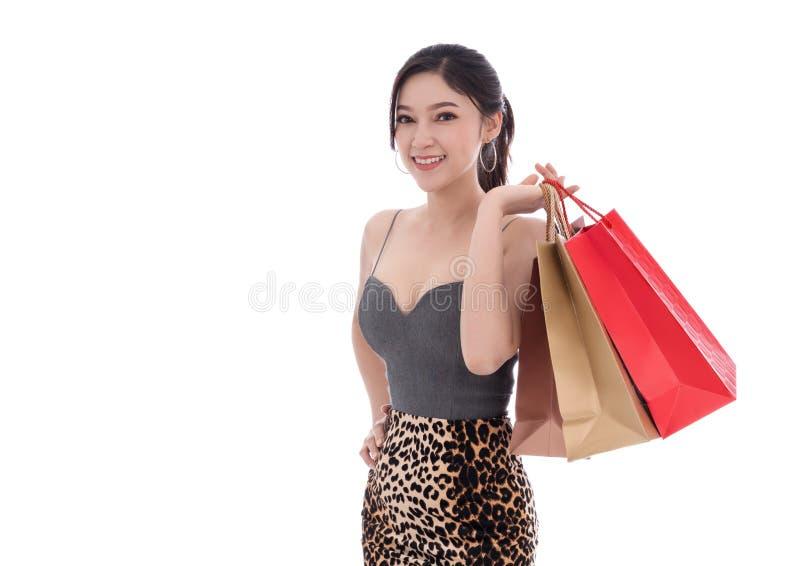 Gladlynt hållande shoppingpåse för ung kvinna som isoleras på vitbaksida arkivbild