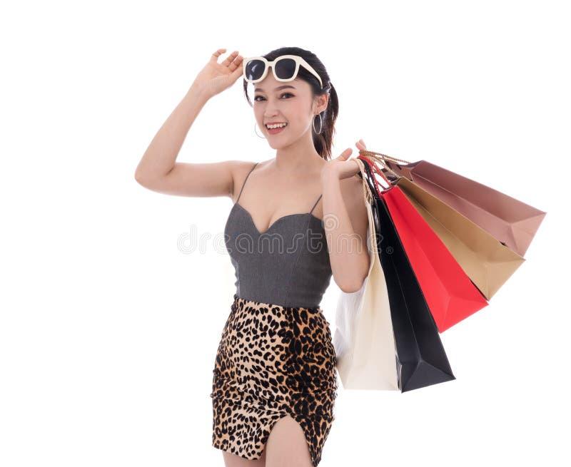 Gladlynt hållande shoppingpåse för ung kvinna som isoleras på vitbaksida royaltyfri foto