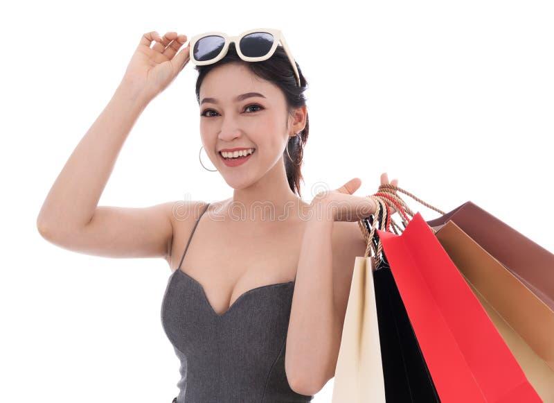 Gladlynt hållande shoppingpåse för ung kvinna som isoleras på vitbaksida royaltyfria bilder