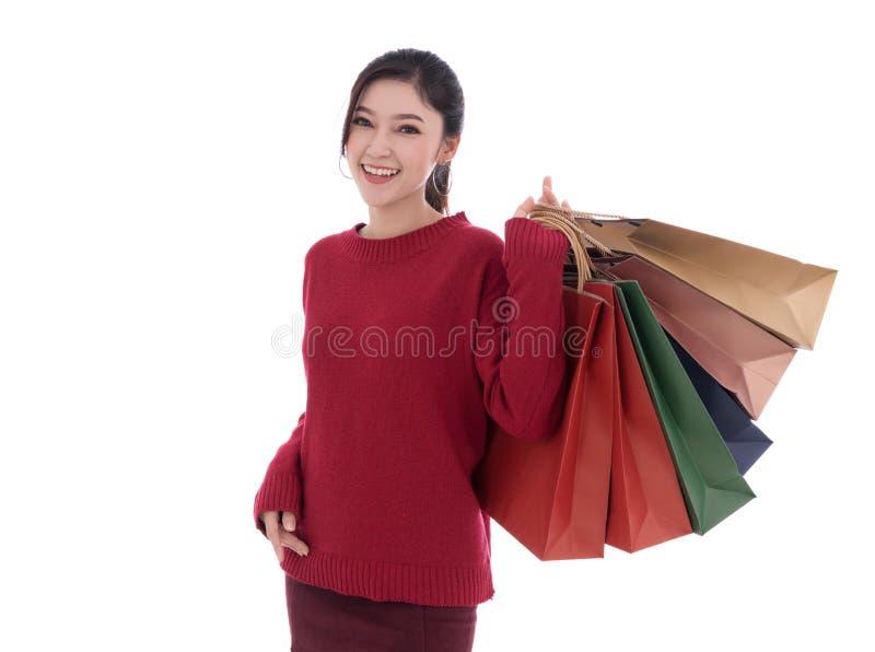Gladlynt hållande shoppingpåse för ung kvinna som isoleras på vitbaksida arkivbilder